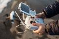Man with remote control prepare white drone digital camera for start flying in winter Royalty Free Stock Photo
