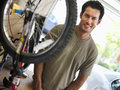 Man repairing bicycle on workbench in domestic garage smiling side view portrait Royalty Free Stock Photography