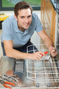 Man Repairing Domestic Dishwasher In Kitchen Royalty Free Stock Photo