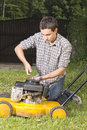 Man repairing yellow lawn mower Stock Photo