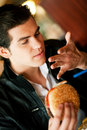 Man in restaurant eating hamburger Stock Photo