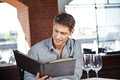 Man in restaurant looking at drinks attractive young a the menu Royalty Free Stock Photo