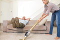 Man resting on couch while woman vacuuming area rug Royalty Free Stock Photo