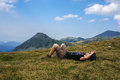 Man resting on the grass in the mountains laying down Royalty Free Stock Photography