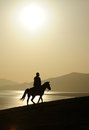 Man ridig horse at sunrise Royalty Free Stock Photo