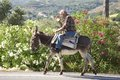 Man riding donkey crete near the village spilli an old with a on the street in the mountains on crete the is still used as a means Royalty Free Stock Photo