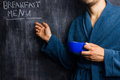 Man in robe pointing at breakfast menu on blackboard a Stock Images