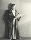 Man in robe reading scroll Stock Photo