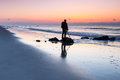 Man on rock at beach silhouette of a standing a folly waiting for sunrise over the atlantic ocean near charleston south carolina Stock Photo