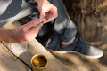 Man rolling a cannabis joint addicted to marijuana or himself sitting outdoors in the shade close up view of the hands Stock Images