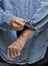 Man rolling up his sleeves in denim shirt Stock Images