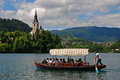 A man rowing a boat on lake bled for group of tourists with famous landmark in the background Royalty Free Stock Photo