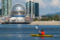 Man rowing a kayak in false creek vancouver with telus world of science the background Royalty Free Stock Photography
