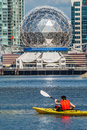 Man rowing a kayak in false creek vancouver with telus world of science the background Royalty Free Stock Image