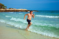 Man is running along the beautiful beach enjoying water Royalty Free Stock Images