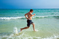 Man is running along the beautiful beach enjoying water Stock Photos
