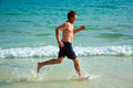 Man is running along the beautiful beach enjoying water Stock Photo