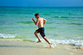 Man is running along the beautiful beach enjoying water Stock Photography