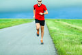 Man running on country road runner in summer sunset young athlete male training for marathon and doing workout outdoors in nature Royalty Free Stock Images