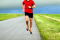 Man running on country road sport training runner summer sunset young athlete male and doing workout outdoors in nature Stock Photography