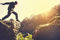 Man running on Mountains jumping cliff over lake Royalty Free Stock Photo