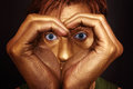Man's face with hands folded in shape of heart Stock Photos
