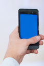 Man's hand holding cell phone with empty blue Royalty Free Stock Photo