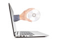 Man s hand holding a disk sticking out of the notebook concept technology Royalty Free Stock Photography