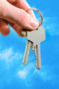Man s hand holding house keys blue sky background Royalty Free Stock Photo
