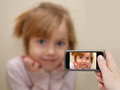 Man's hand making photo of a little girl with a mobile phone. Royalty Free Stock Photo