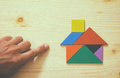 Man's hand pointing at house made from tangram puzzle Royalty Free Stock Photo