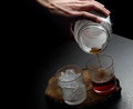 Man s hand pouring hot and cold coffee into two glasses dark background Royalty Free Stock Photos