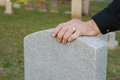 Man's hand resting on headstone Stock Image
