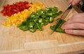 Man`s hands cutting delicous paprika in the kitchen, preparing a meal for lunch. Macro shot. Royalty Free Stock Photo