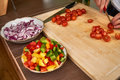 Man`s hands cutting fresh tomatos in the kitchen, preparing a meal for lunch. Side view. Royalty Free Stock Photo