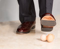 Man's shoe stamping on three eggs Royalty Free Stock Photography