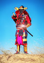 Man in samurai costume pulls out his powerfull hot sword men on the sand original character Royalty Free Stock Photos