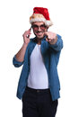Man with santa claus hat talking on phone and pointing young casual is the to the camera Royalty Free Stock Image