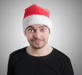 Man with a santa hat on grey background Royalty Free Stock Image
