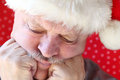 Man in santa hat looking depressed unhappy older with hands against cheeks Stock Photo