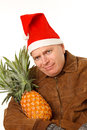 Man in Santa hat with pineapple. Royalty Free Stock Photo