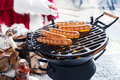 Man in santa outfit grilling sausages outdoors the snow on a portable barbecue close up of his hand a christmas party Stock Image