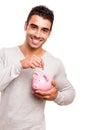 Man saving money to a piggy bank Royalty Free Stock Photo