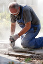Man sawing stone with grinder hard working bearded safety glasses and gloves real photo Royalty Free Stock Photos