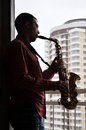 Man with saxophone handsome young playing on outdoor Royalty Free Stock Image