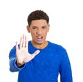 Man saying no stop here closeup portrait of handsome unhappy mad young raising hand up to say right there isolated on white Stock Photos