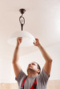 Man screwing a new lightbulb into ceiling lamp electrician closeup Royalty Free Stock Images