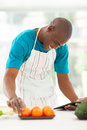 Man searching recipe african american in kitchen for a on tablet computer Royalty Free Stock Photo
