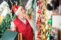 Man selecting christmas ornaments senior in santa hat at store Royalty Free Stock Image