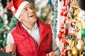 Man selecting christmas ornaments at store happy senior Royalty Free Stock Images